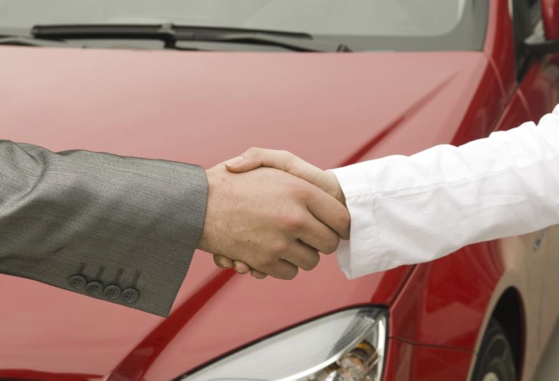 Händeschütteln mit Auto im Hintergrund